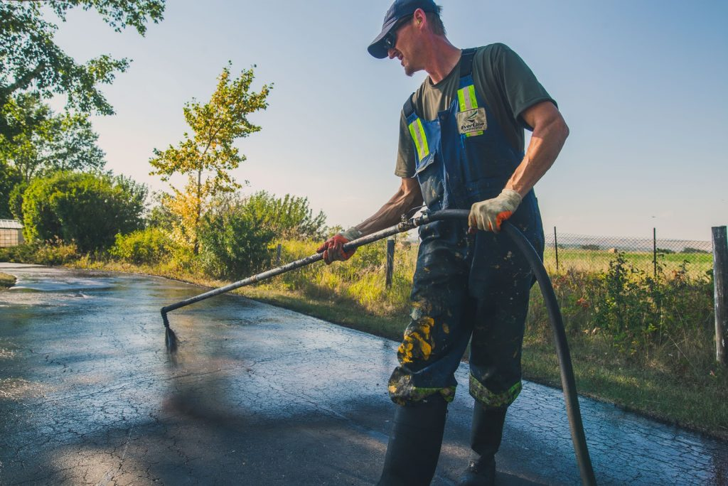 Man spraying sealcoating on asphalt surface