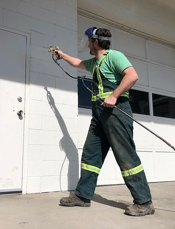 An EverLine crew member disinfecting a doorway