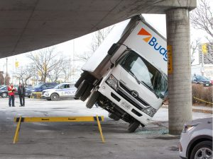 A truck wedged under a parkade ramp