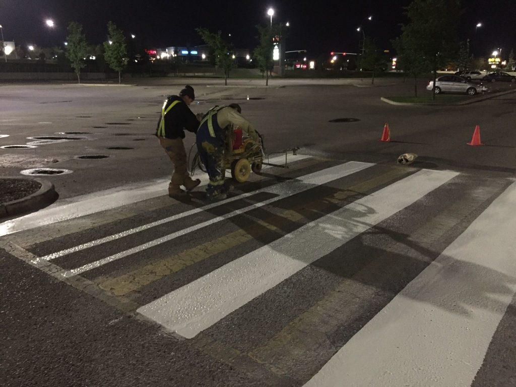 Line painters using line paint to paint a crosswalk